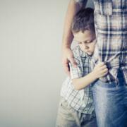 sad boy clutching father